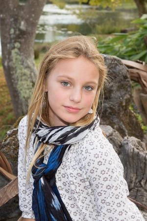Lovely blonde teen girl smiling in grass