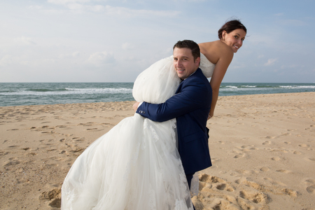 trash the dress: Bride and groom sharing romantic and happy moment at beach Stock Photo