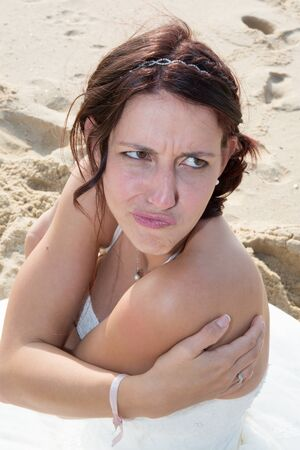Head shot of bride or woman scowling at beach
