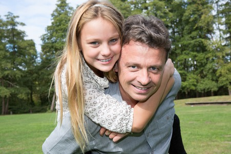 Cheerful father giving daughter piggyback at park Stock Photo
