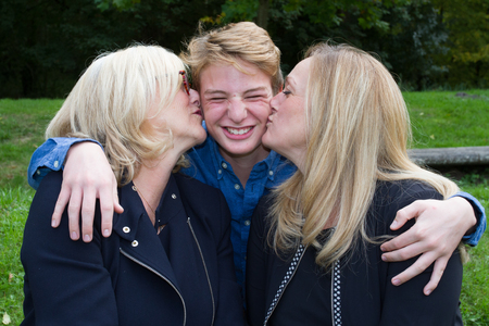 grand son: Grand mother and daughter kissing son outside