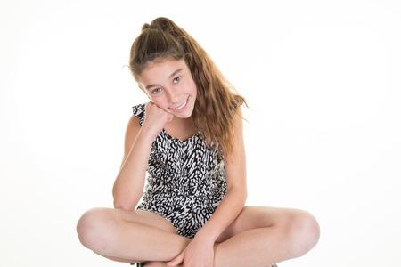 Pre-teen girl sitting cross-legged isolated on white Stock Photo