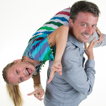 pre teen: Dad playing with his happy pre teen daughter, holding her upside down,