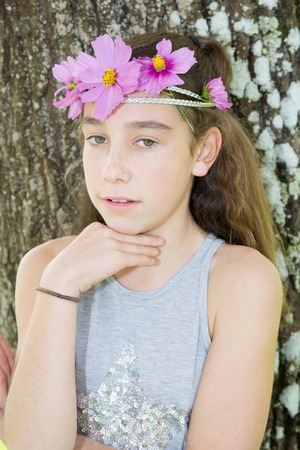 pre adolescence: Cute brunette with floral headband on head