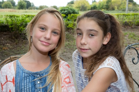 Two Girls in park, blond and brown hair girl