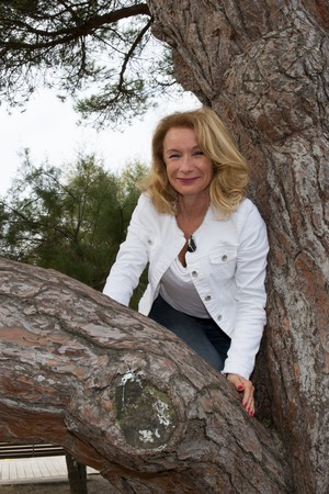 leaning against: Middle-aged blond pretty woman leaning against tree