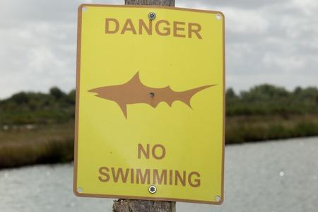 no swimming sign: Shark warning yellow sign on the beach Stock Photo