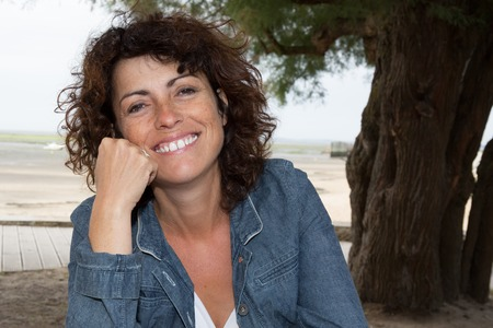 fourties: Happy woman with brown hair in her fourties smilling outdoors Stock Photo