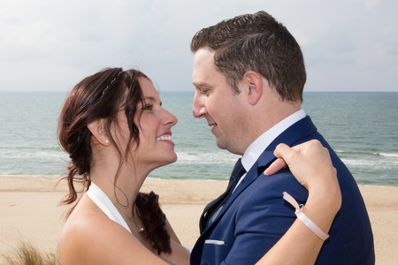 In love couple at beach with a wedding dress