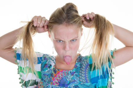 Young blond pretty girl puts out her tongue isolated Stock Photo