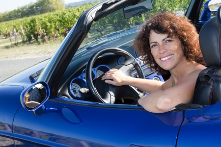 cabriolet: Woman in cabriolet car in vineyard smiling