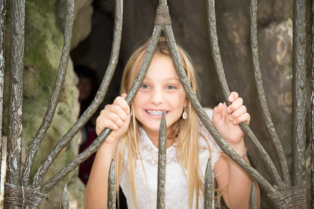 ebullient: Blond preteen girl with very blue eyes behind iron gate Stock Photo