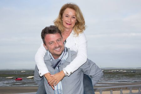 caribe: Loving middle-aged couple at the beach piggy back