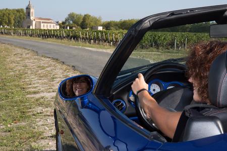 wine road: Woman in convertible car in vineyard looking in her mirror