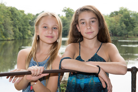 Two preteen blond and brunette girls close to the river