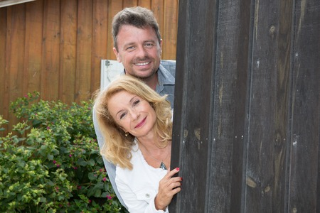 forties: Portrait of middle aged couple standing outside the house