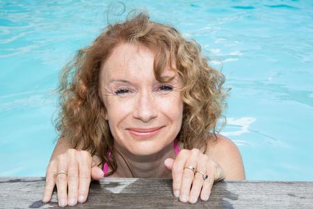 Femme blonde tient le desck de la piscine
