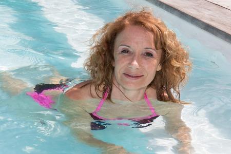 Enthousiaste femme âgée blonde dans la piscine