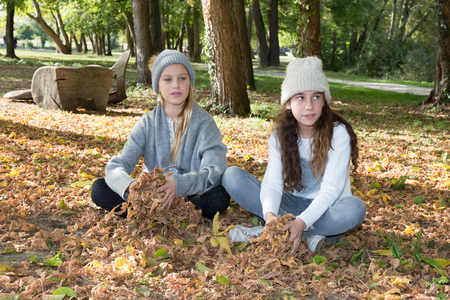 lass: Two adorable school aged girls friends having fun in the autumn