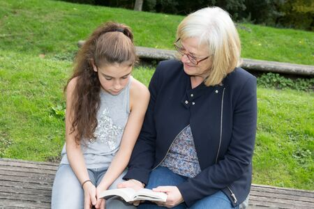 the grand daughter: Portrait of a grand child and granddaughter reading a book outdoors Stock Photo