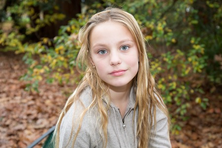 Thoughtful blond preteen girl looking at camera