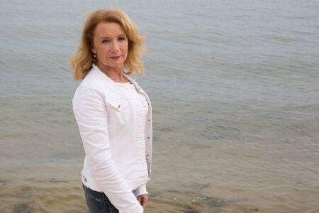 Ältere Frau vor Ozean Strand im Winter