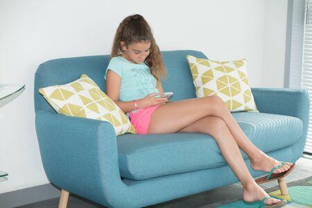 scandinavian girl: teenager girl playing with phone in modern scandinavian house