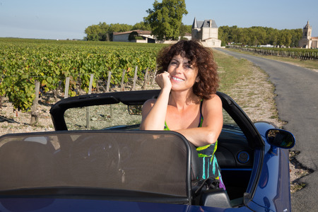 wine road: lovely forties woman in convertible car in wine road tourism