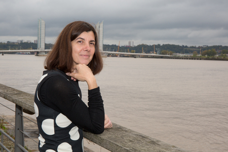 forties: woman forties near river in city