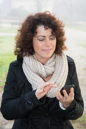 forties: forties woman texting with phone in a parc
