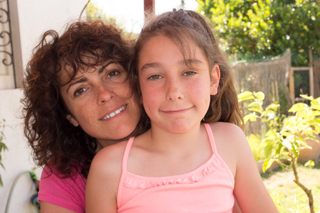 forties: forties mother with ten years old girl in garden during summer