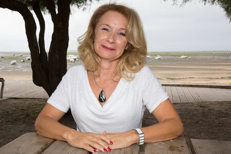 pretty senior woman holidays in town beach on summer Stock Photo