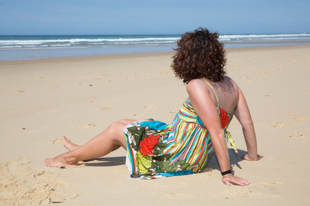 A woman looks at the beach in summer alone Stock Photo