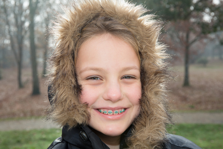 pretty young blonde girl outdoor with dental braces smiling