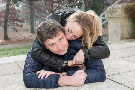 forties: blonde forties woman kissing her husband outdoor, lying on the park on autumn Stock Photo