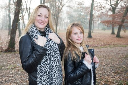 complicity: A blonde mother and her daughter play in the autumn park in complicity Stock Photo