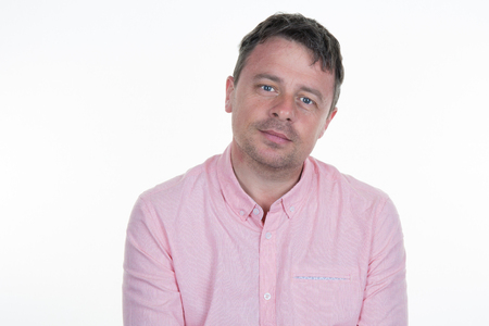 Portrait of a thirties man with a pink shirt on a white background Stock Photo