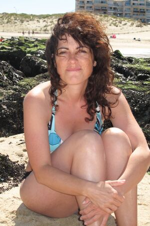 beachfront: A cute and charming single woman sits on the beachfront