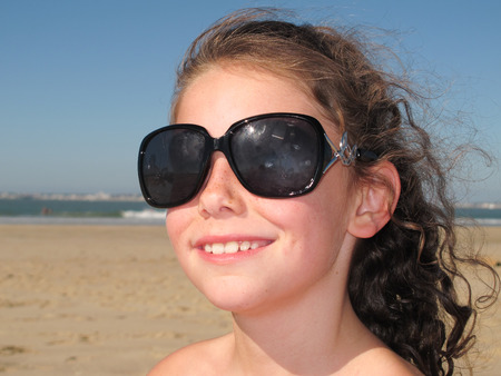A girl on the beach with old sunglasses