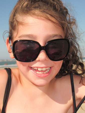 Portrait of a funny and smiling girl with sunglasses