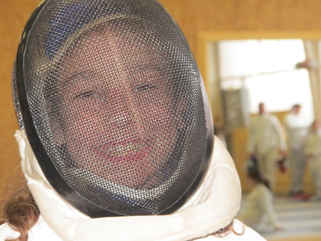 are thrust: A girl who smiles with her fencing helmet