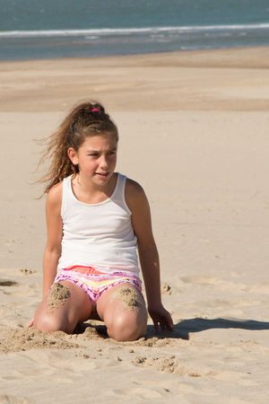 a girl during the summer kneeling on the sand Stock Photo