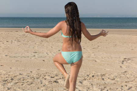 A young girl doing yoga on the beach during the summer