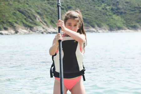 girl child doing paddle on a lake with her ream