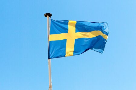 flag of Sweden in the wind and a blue sky Stock Photo