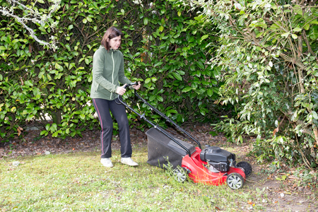 mows: woman mows the lawn between the trees in her garden