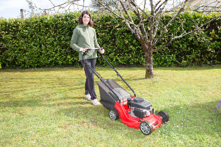 woman passes the lawnmower in the family garden