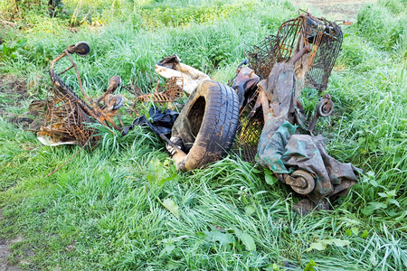 Tires and pieces of supermarket trolley thrown into a field in nature Stock Photo