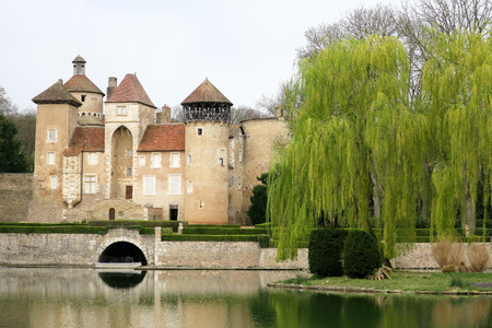 beautiful classic castle in the south of France with moat and a beautiful weeping willow