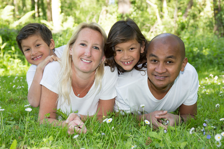 mixed family of four lying on grass with blond and indian parents